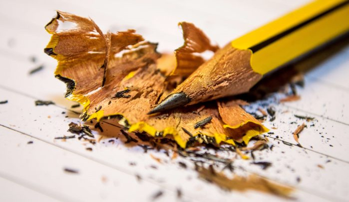 Tip-of-sharpened-yellow-pencil-laying-on-pencil-shavings