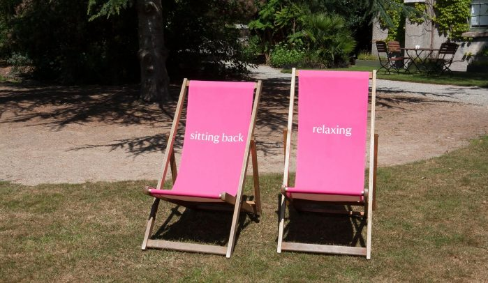 Two-pink-deckchairs-on-lawn