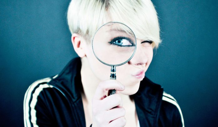 Woman-with-short-blond-hair-looking-through-a-magnifying-glass