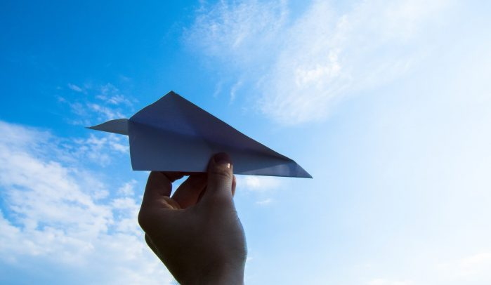 Hand-launching-paper-plane-into-blue-sky