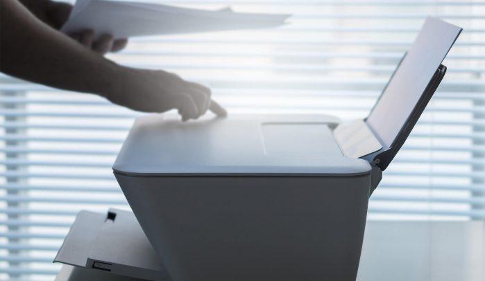 Hand-pressing-button-on-inkjet-printer