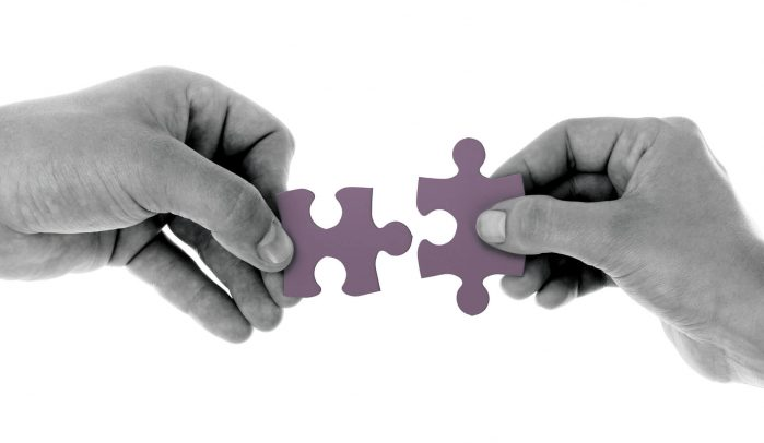 Two-hands-bringing-together-fitting-jigsaw-pieces