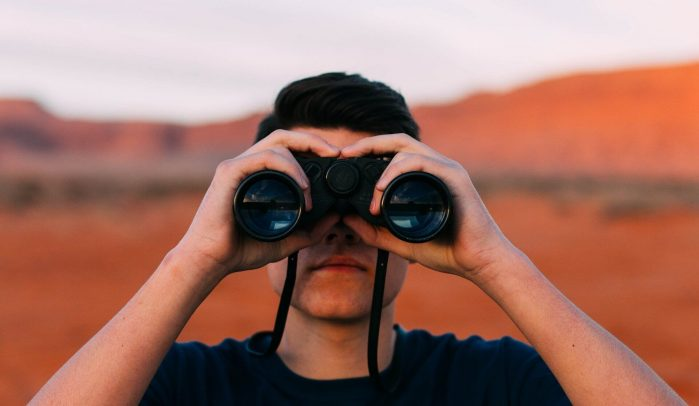 Man-looking-through-binoculars-in red-landscape