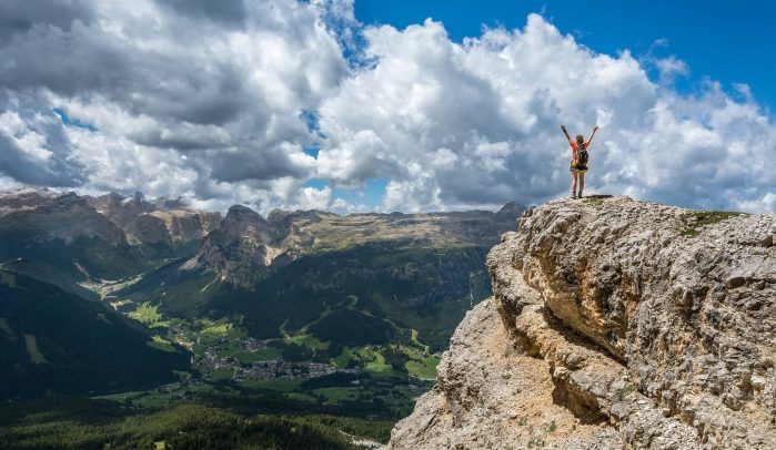 Woman-with-arms-in-the-air-standing-on-top-of-a-mountain