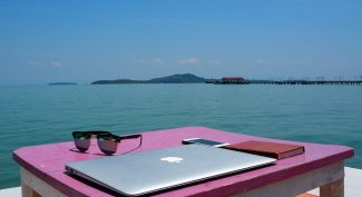 Pink-wooden-desk-with-laptop-by-the-sea-in-Thailand
