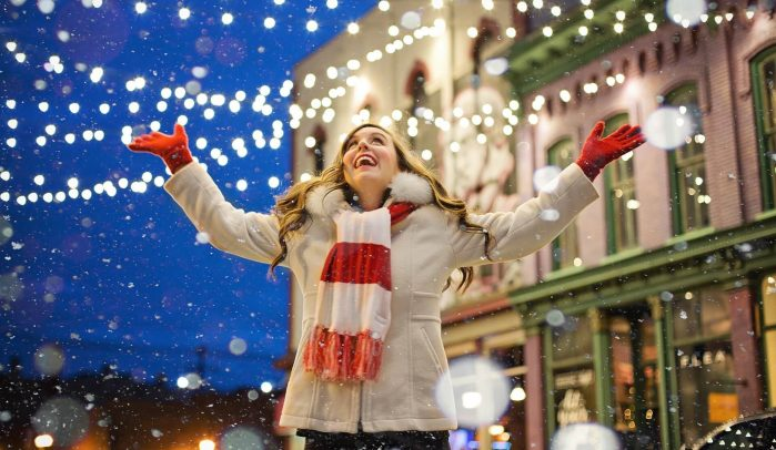 Excited-woman-standing-in-winter-street-with-twinkly-lights