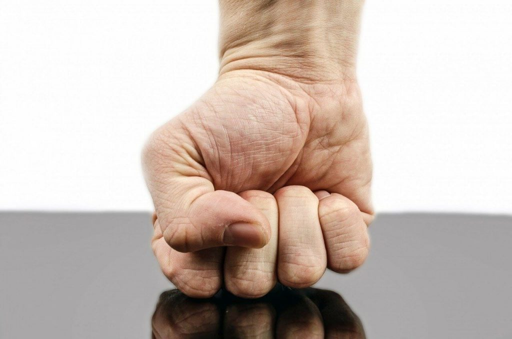 White-male-fist-punching-tabletop