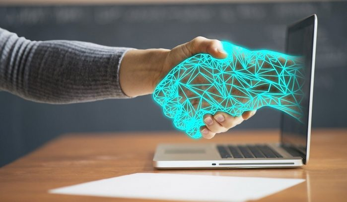 Human-hand-shaking-computerised-hand-coming-out-of-a-laptop-screen